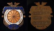 Enamelled metal shield shaped medal with text and designs on the front and inscribed and embossed text on the back