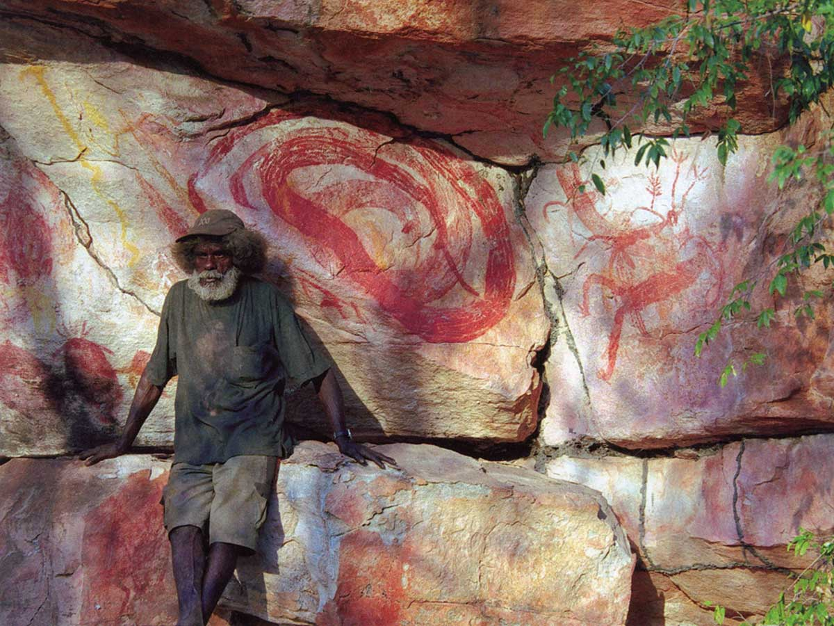Colour photograph of a man sitting in front of rock paintings.. - click to view larger image