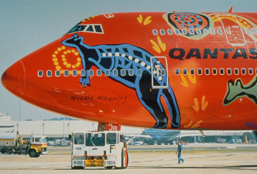 Side view of the front section of a large 'QANTAS' aircraft painted with a red background and multicoloured Aboriginal designs, including a large kangaroo.