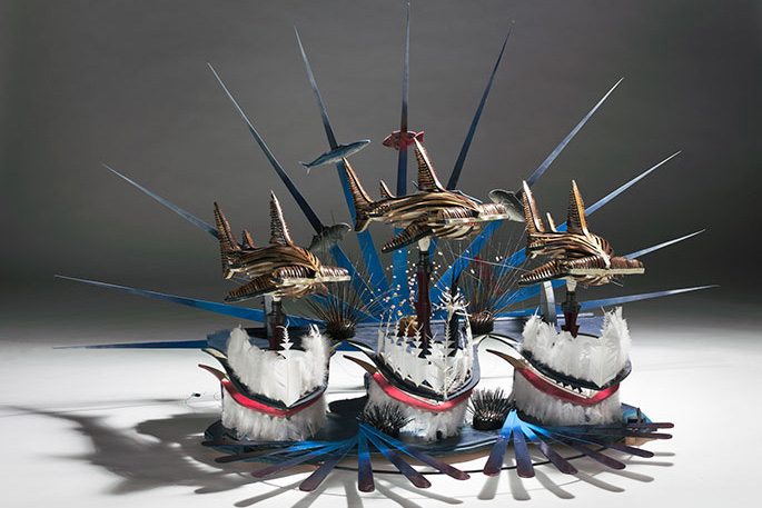 A Beizam headress with a blue spiked fan at the back, three brown cane hammerhead sharks in front, above three shark jaws of wood and black and white feathers on layered boards, joined by central posts. Between the shark jaws and behind the top central jaw, are discs with thin metal wires coming out of the top of them. At the front are two blue and red fans with rounded ends extending from between the shark jaws. The fan at the back has bright coloured fish cutouts atatched to the blades. The sharks and the front fans are joined by wires.