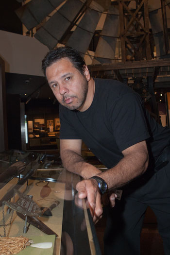 A man leans on a glass display case containing a number of objects. A large windmill can be seen in the background.