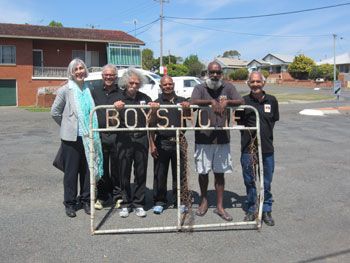 "A group of people stand behind an old metal gate. The gate contains the writing ""Boys Home""."