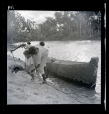 A black and white photographic negative that depicts an Aboriginal child and three adults standing on the edge of a riverbank next to a canoe.