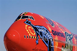 Front of a large aeroplane, painted in Aboriginal designs on a red backdrop.