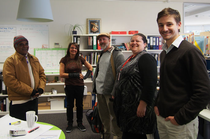Five people stand in an office smiling for the photo.