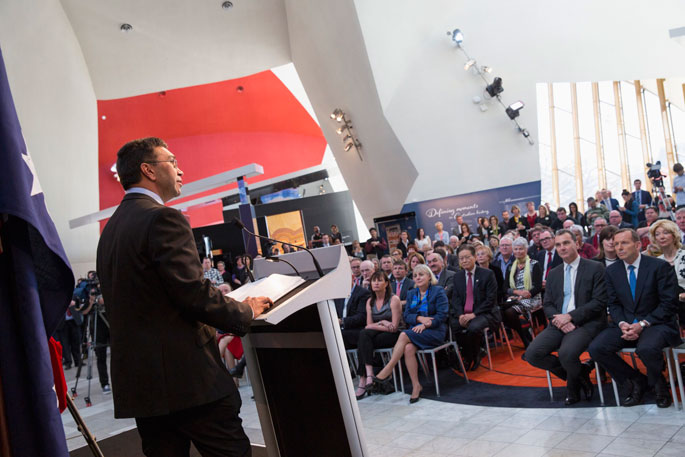 A man at a lecturn addresses a crowd.