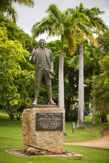 Statue of Captain Cook in naval dress and holding charts atop a stone base and a plaque headed 'Captain James Cook'.