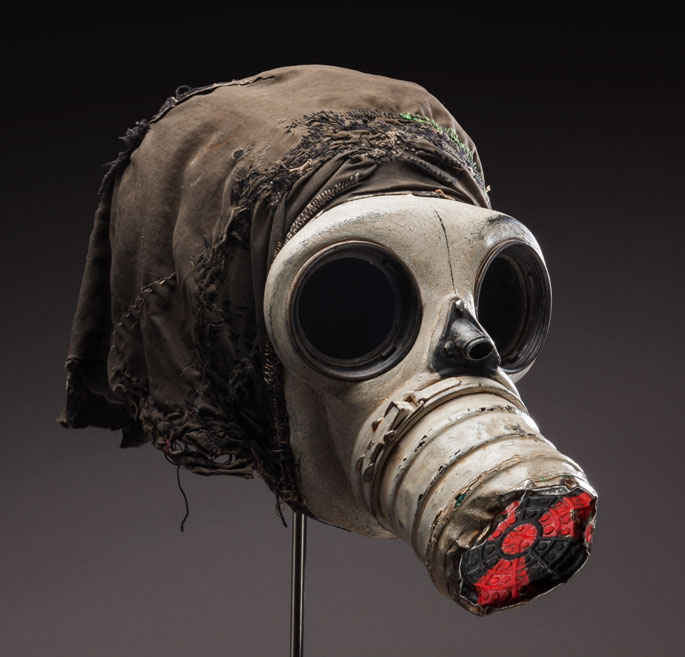 Gas mask with black cloth attached to the back and the international symbol for radiation painted in red on the nose cone.