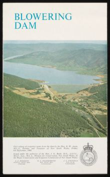 Cover of a booklet titled 'Blowering Dam' showing an aerial photo of a large dam and surrounding landscape. Text and a small crest also feature at the bottom.