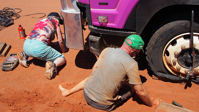 A man and a woman kneeling on the ground next to the wheel at the front of a purple truck.