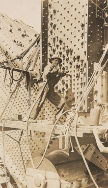 A man using a hand-held rivet gun during the construction of the Sydney Harbour Bridge.