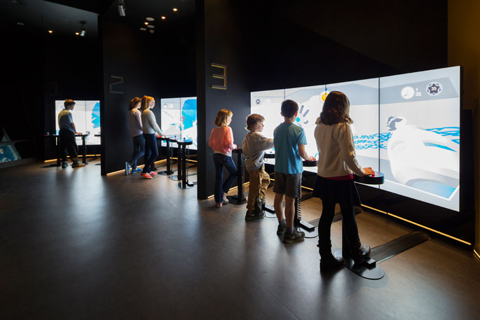 Several children in front of large display screens, playing Kspace.