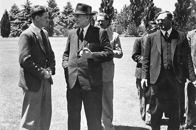 Outside photo of young man with folded hands talking to a smiling Prime Minister Chifley. Calwell stands to one side.
