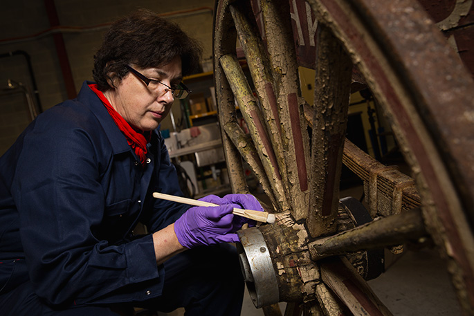 Conservator Kathryn Ferguson treating a 1930s bakery cart for display in Spirited: Australia's Horse Story