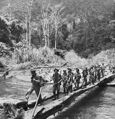 About 20 soldiers use a simple bridge that is little more than a pair of logs.