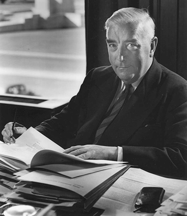 Menzies at his desk in Parliament House with piles of paper in front of him.