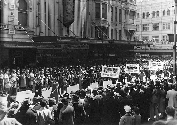 Black and white photo showing men and women marching down street lined with crowds. Workers are holding banners such as Equal pay for female workers.