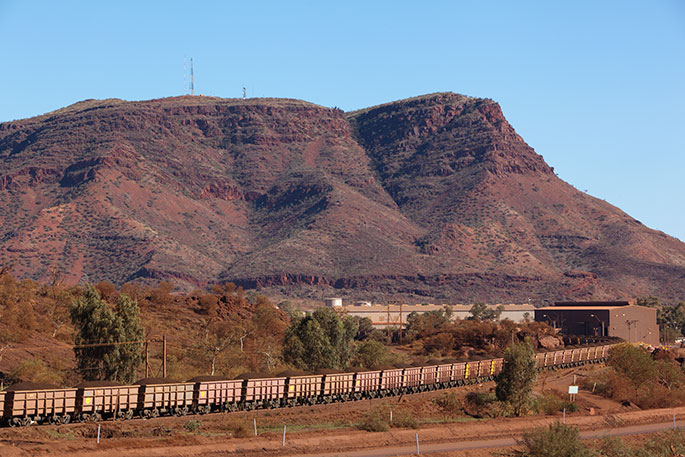 Long train with bogeys bulging with iron ore. In background is a low mountain.