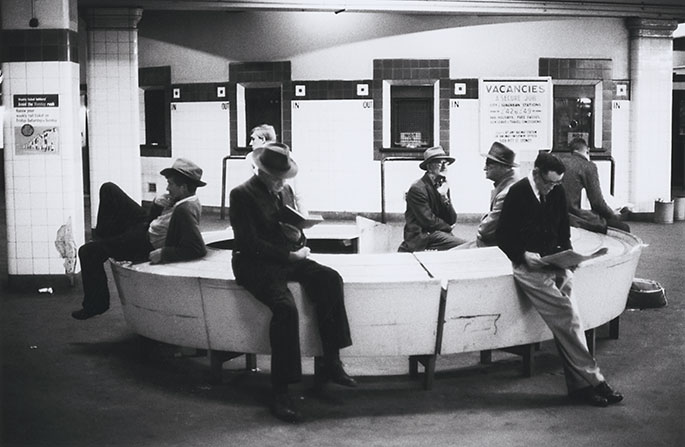 Interior photo of seven men sitting on a circular bench cum table. A few of them are reading but most are doing nothing at all. In the background are the station's ticket booths. Next to one of these is a poster advertising railway jobs.