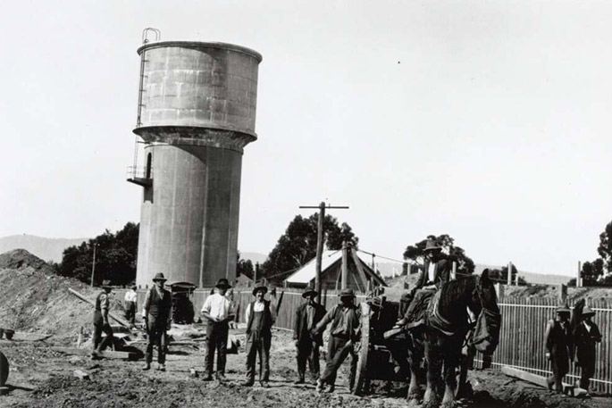 A dozen or so men at work on a suburban construction site, most of them posing for the camera. A draught horse attached to a cart stands among them eating from a nosebag. They appear to be clearing land. A water tower and suburban roofs are visible in the background