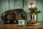 A photograph of an old radio, a teacup, a vase of flowers and a plate of biscuits.