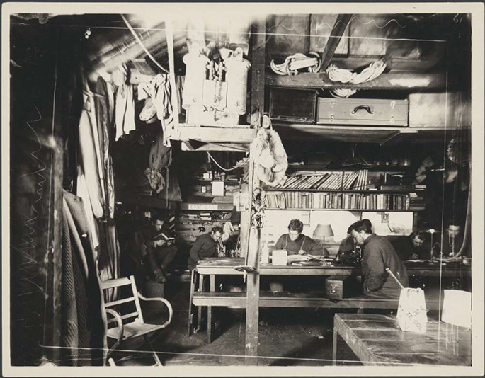 black and white photo of men inside hut