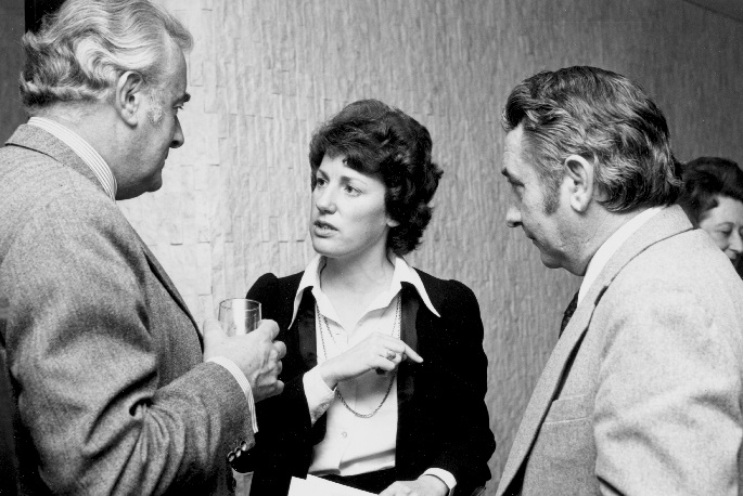 Interior photo. Woman in her thirties is speaking while Whitlam and Oswin listen