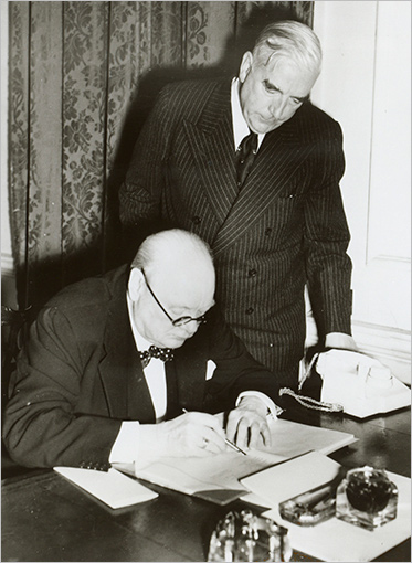 Churchill is at a desk examining some documents. Menzies is standing beside him, looking over his shoulder