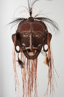 Cultural mask with brown face, white markings, feathers and other materials.