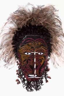 Cultural mask with brown face; red, yellow and orange markings; feathers and other materials.