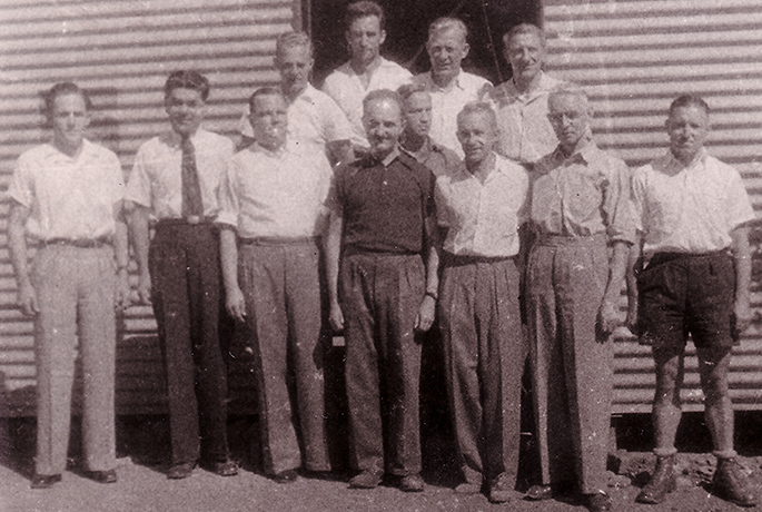 12 men, mostly wearing shirts and long pants, standing in front of a corrugated iron structure
