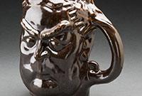 Brown glazed jug depicting a man's head