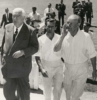 Menzies in suit and Dexter and Bradman in cricket whites to his left