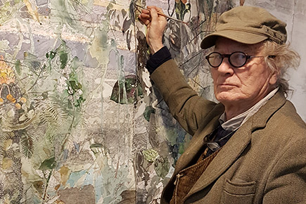 an older man dressed in a brown suit with matching cap and wearing spectacles is holding a paint palate in one hand and a paint brush in the other. He looks as if he is putting the finishing touches on a large painting attached to the wall.