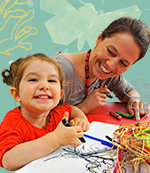 A woman and child seated at a table and undertaking craft activities