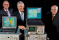 : three men in suits standing beside a table on which sit a collection of cumbersome electronic equipment.