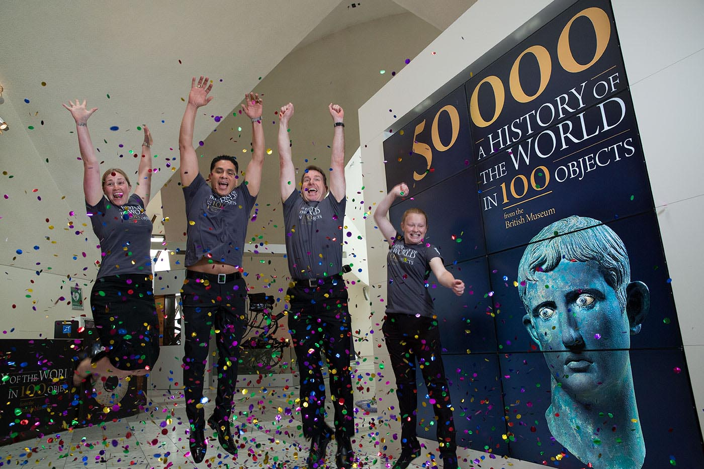 Two women and two men in uniform jumping in the air amidst confetti, adjacent to a promotional billboard.