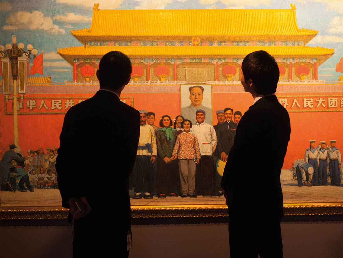 A colour image of two people dressed in dark suits viewing a large painting mounted on a wall.