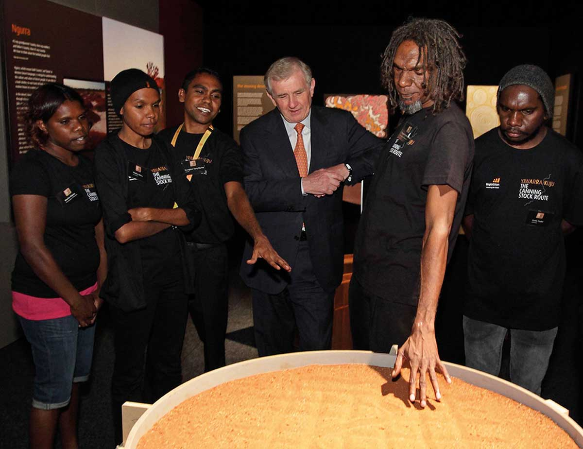 A group of people surrounding an object containing sand.