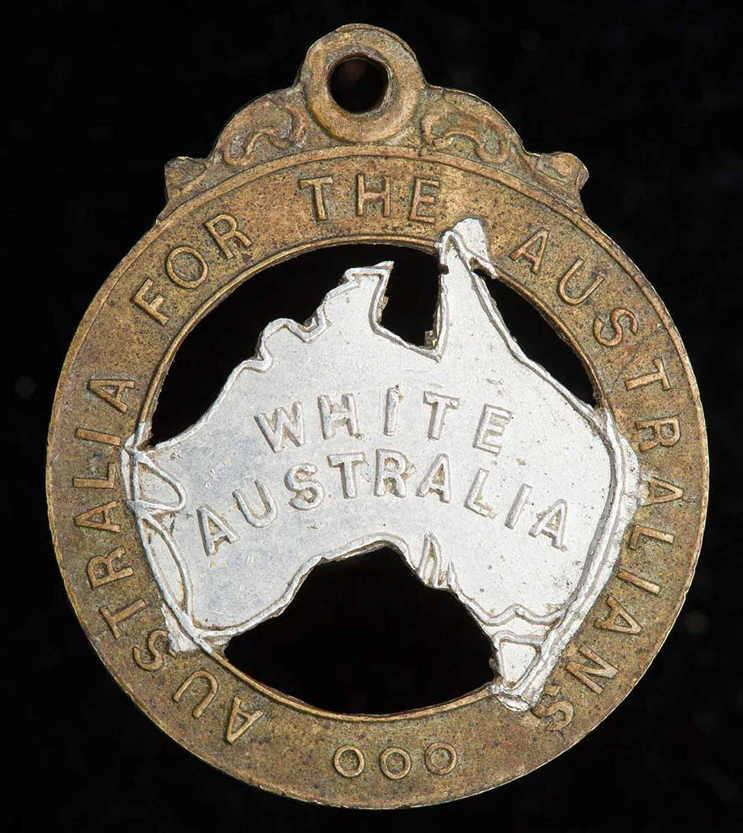 This 28mm-high badge has the words 'Australia for the Australians' stamped on the rim and the words 'White Australia' stamped on silver-painted representation of the Australian continent in the middle. - click to view larger image