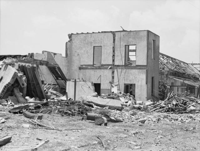 A badly damaged building, surrounded by rubble.