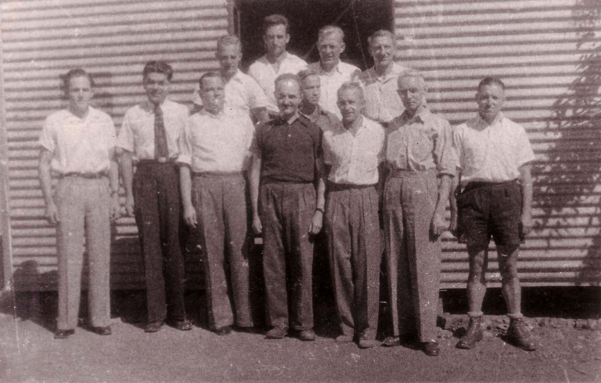 12 men, mostly wearing shirts and long pants, standing in front of a corrugated iron structure.