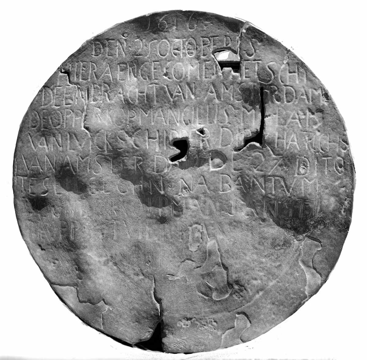 A battered disc, much worn and with holes in it. Words are visible, neatly inscribed in capitals in the top two thirds of the plate. - click to view larger image