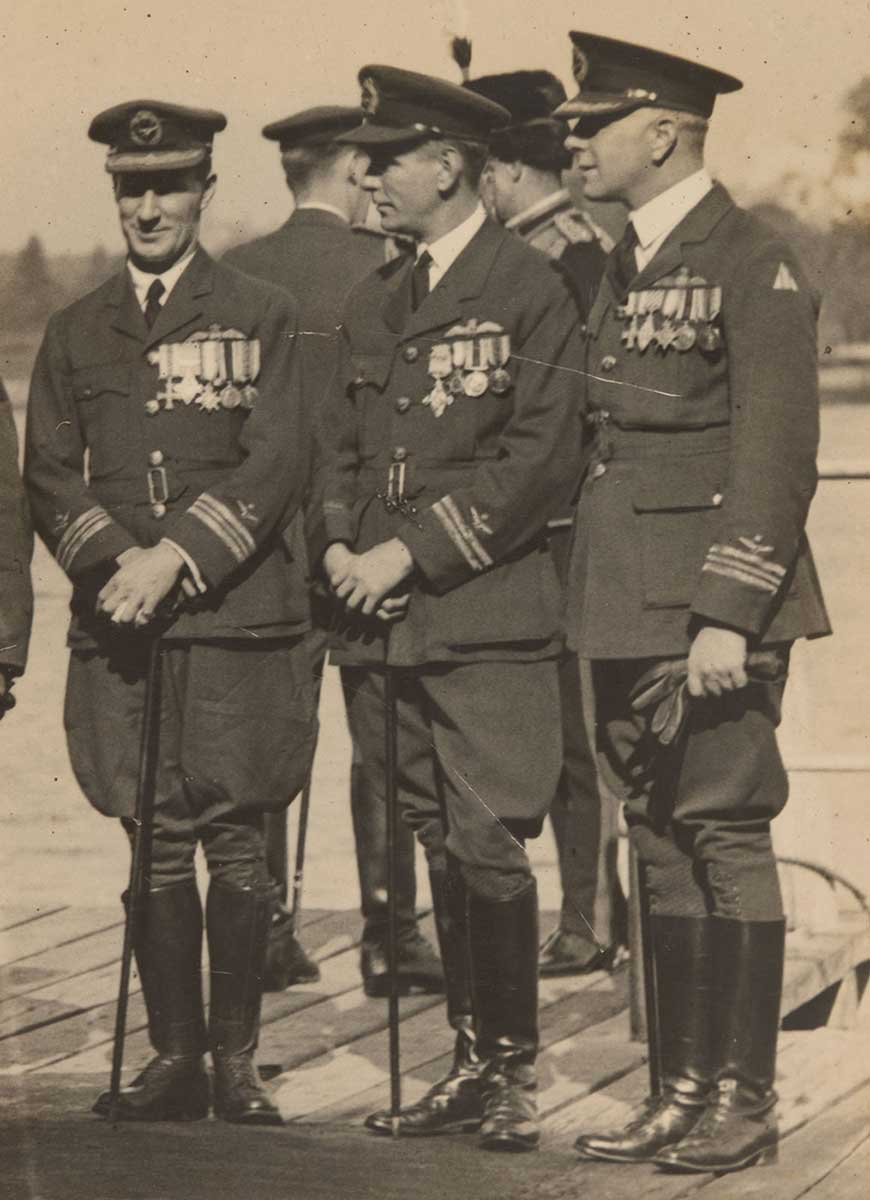 A black and white photo of Kingsford Smith in full RAAF uniforms with canes. - click to view larger image