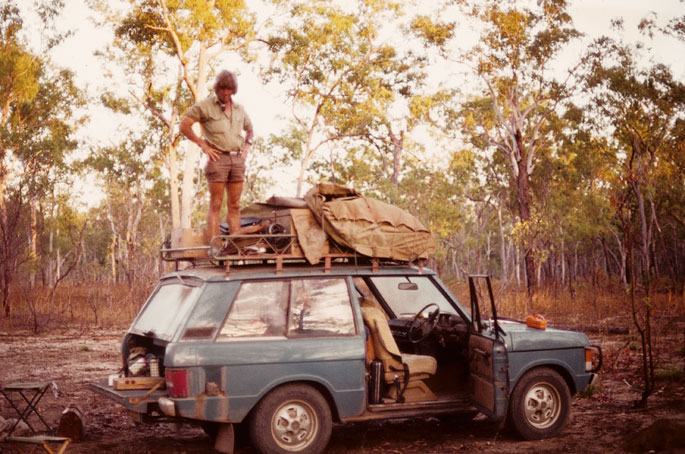 Fred Hollows, in khaki shirt and shorts, stands on the roofracks of a four-wheel-drive vehicle. Various equipment is packed onto the roofracks. The vehicle is parked in a clearing surrounded by tall trees.