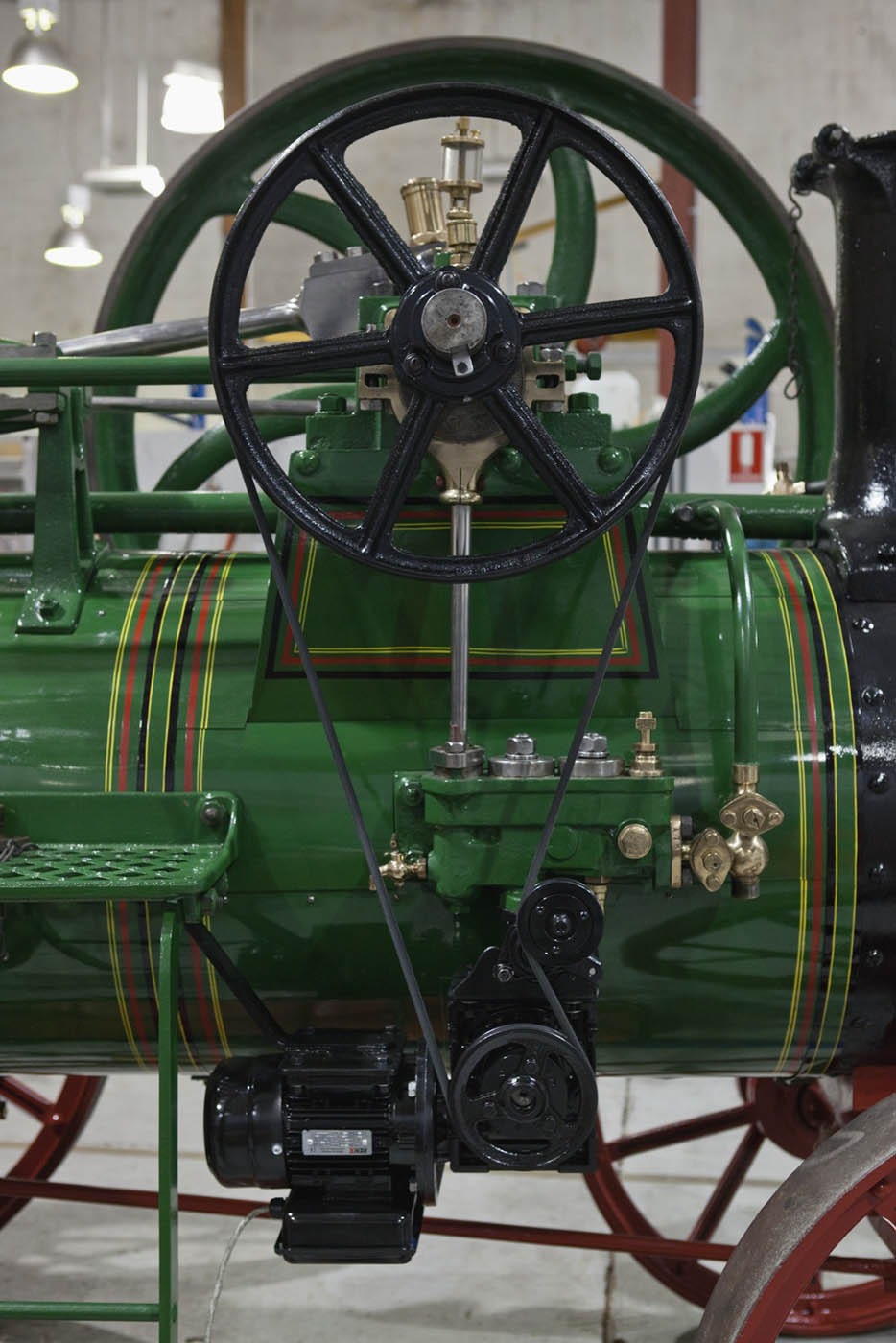 A colour photograph of the engine's large flywheel, attached by a belt to a smaller pulley below.. - click to view larger image