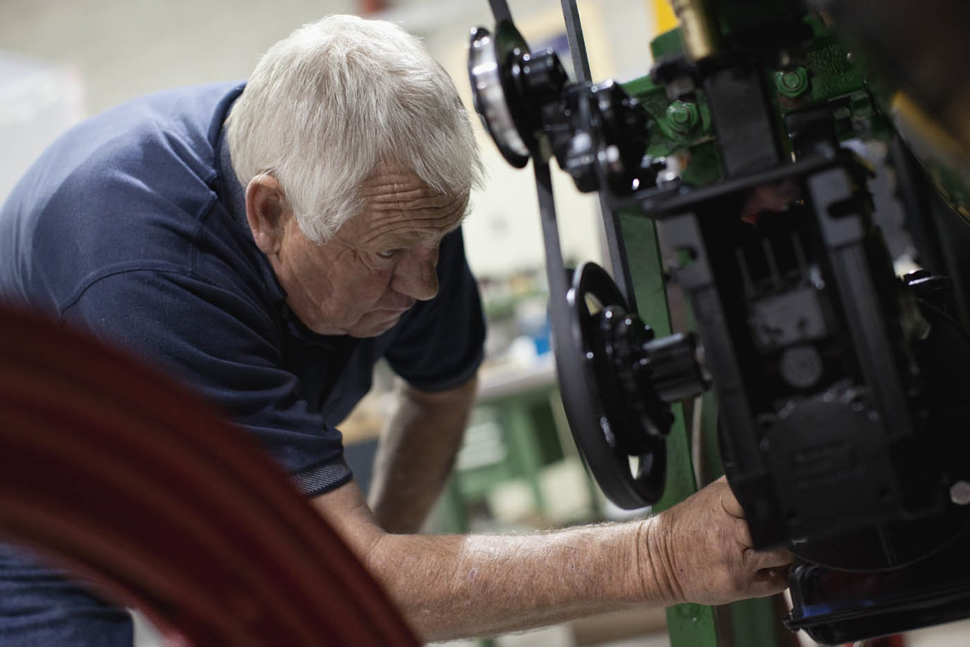 A colour photograph of a man working on an engine. - click to view larger image