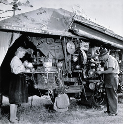 A black and white photograph of Harold Wright and his daughter Evelyn with the Saw Doctor's Wagon, 1956