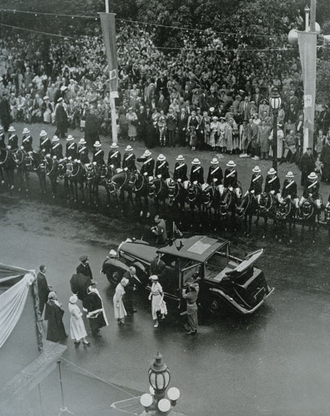 Queen Elizabeth is seen from above, walking from a vehicle toward a building. Behind the vehicle are what appear to be many police on horses lining the edge of the road upon which the vehicle is parked. A group of people wait near the building, apparently ready to greet the Queen. - click to view larger image