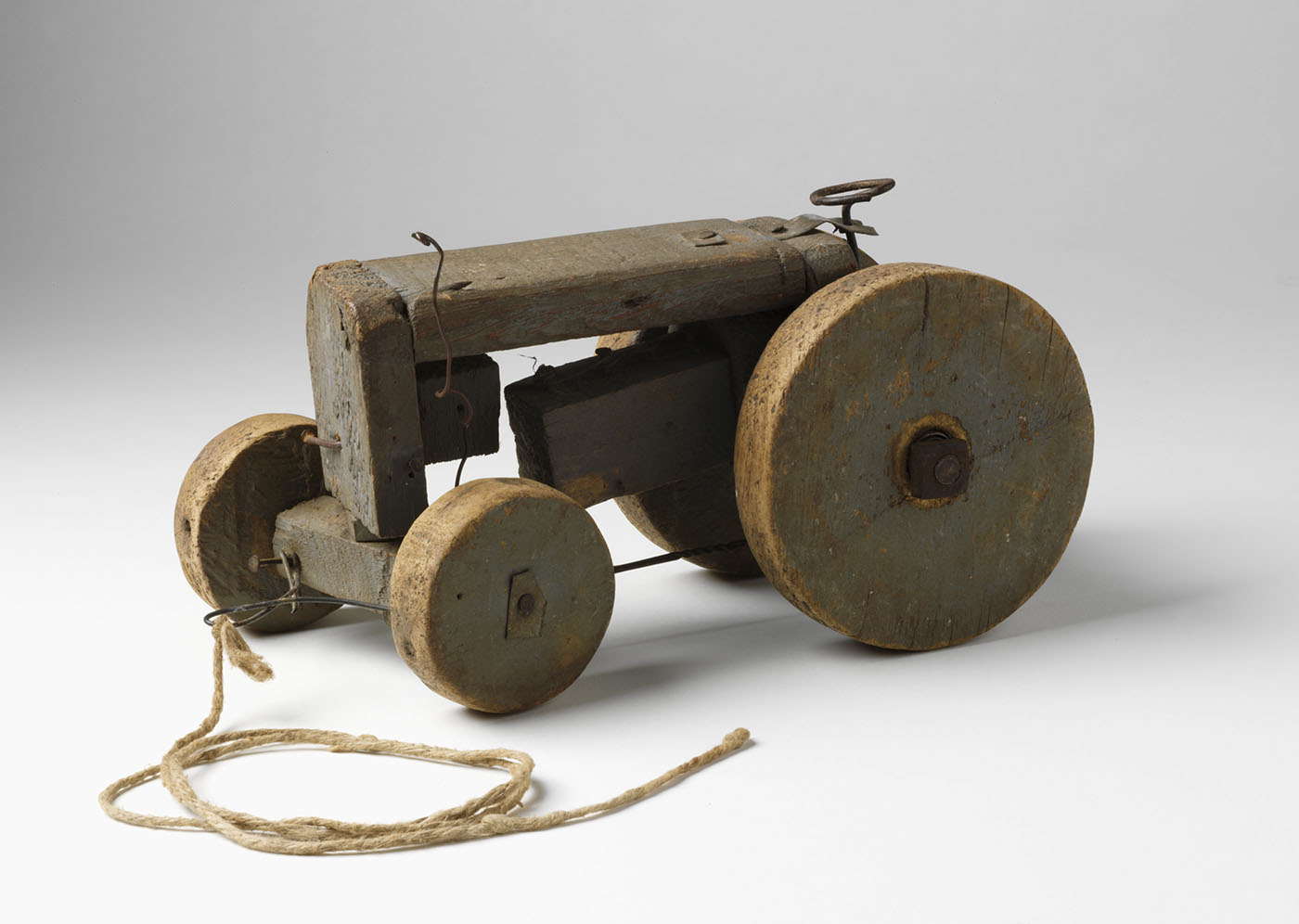 Toy wooden tractor constructed from timber and wire with two larges wheels at the rear and two small wheels at the front.